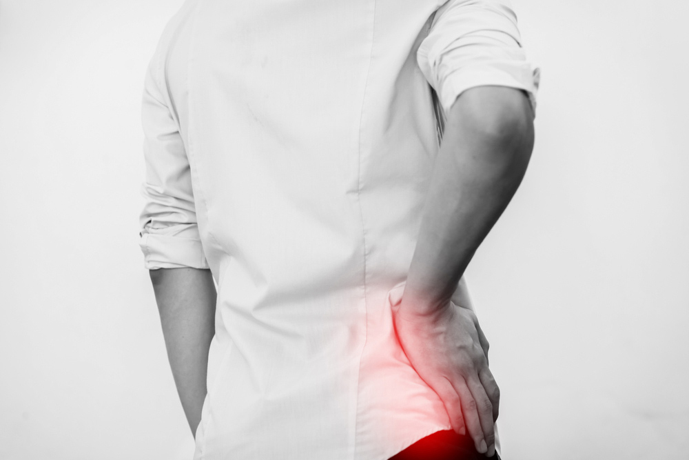 man with sciatica pain holding back before seeing an Irvine Chiropractor